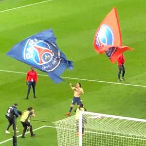 Cavani celebrating PSG winning the title by waving a giant PSG flag