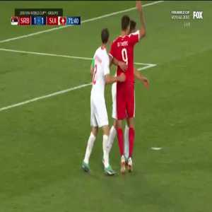 Serbian player tackled by Swiss defenders in the box