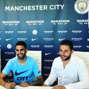 Mahrez pictured signing for City.