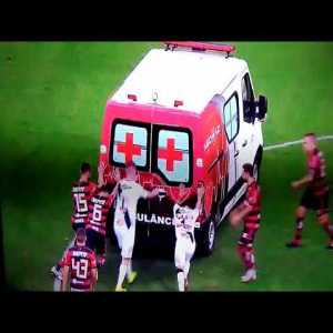 Flamengo and Vasco players push starting the stadium's ambulance. The injured player being taken to the hospital is Bruno Silva (Vasco).