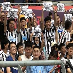 """Newcastle United's local Chinese fan base make their feelings clear about the club's owner inside the Nanjing Olympic Stadium and hold up """"Ashley Out"""" posters"""
