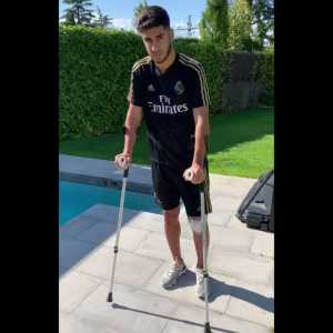Two weeks since his operation after ACL injury. Marco Asensio walks with crutches.