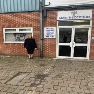Ex Bury director Joy Hart has chained herself to an entrance at Gigg Lane stadium as a protest against current owner Steve Dale