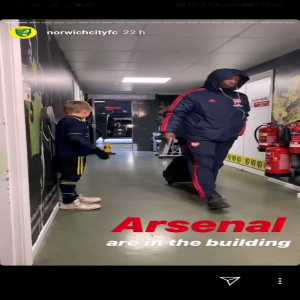 Arsenal players ignore their young mascot as they enter Carrow Road on Sunday