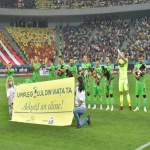 """[VarskySports] Romanian football launched the """"Fill a void in your life"""" campaign to motivate people into adopting abandoned dogs, where team players hold a dog each with their name written in a scarf they wear prior to kick-off"""
