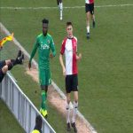 Isaac Success accidentally pushes the linesman over an advertising board