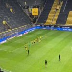 Dortmund players celebrate in front of an empty Südtribüne following their win