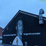 A young boy standing in the shadow of a mural to his hero. Withington, Manchester, UK.